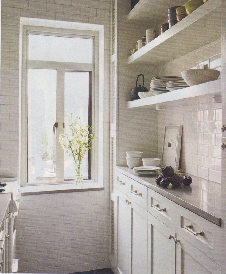 Grey paperstone counter with white cabinets and floating open shelves