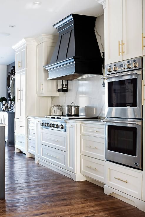 Beautiful white and black contemporary kitchen is fitted with a stainless steel cooktop fixed above white pot and pan drawers and between white drawers donning brushed brass pulls and a white marble countertop fixed against a marble slab backsplash.