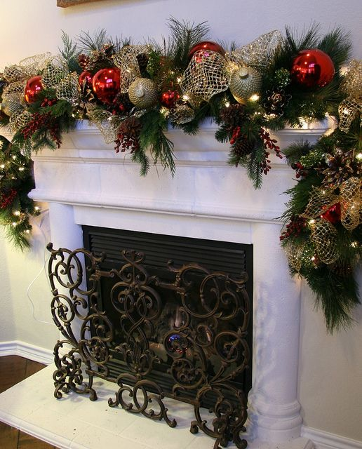 Christmas Fireplace Mantel decorated with greenery garlands and ornaments.