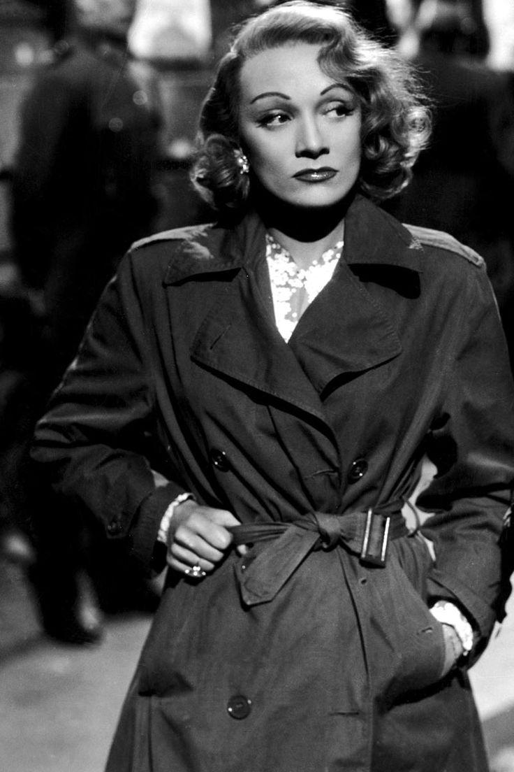 Hitchcock quería una diva real para representar el papel de diva en la ficción en su película Pánico en la escena (1950) y quién mejor que Marlene Dietrich para llenar la escena con su glamour y sofisticación. En la imagen, con un trench y pendientes de perlas.