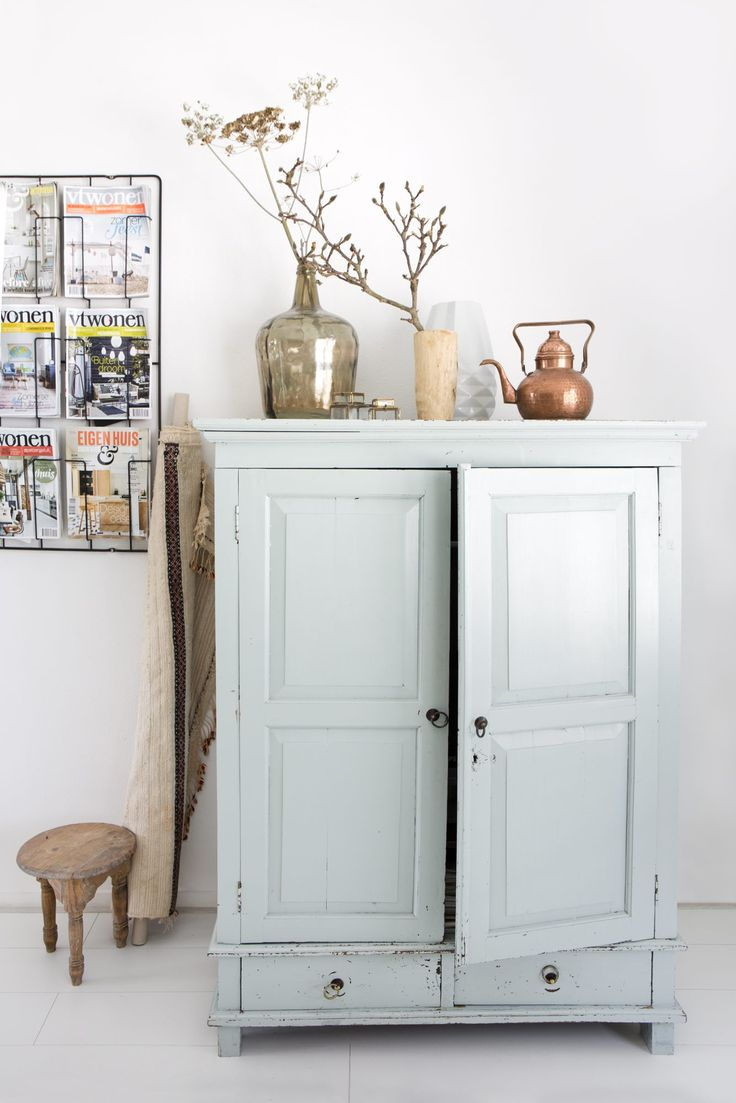 Adorable pale teal armoire in the cutest little apartment shared by a family of 5!