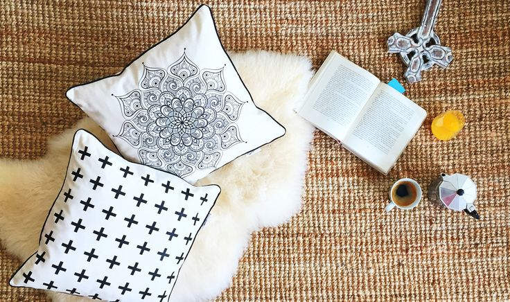 Interior photograph with cushions and white old style looking cross. Morning idyllic scene at home on the floor. Mandala pattern, cross pattern design. Coffee, orange juice, carpet, book, religion, Christianity, Top view