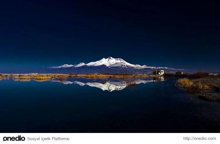 """Kayseri'nin simgesi; Erciyes Dağı-Erciyes Dağı, 3.917 m. yüksekliği, bulutları delen zirvesi, tepesinden eksik olmayan karı ile Kayseri'nin sembolüdür.  Sönmüş bir """"küme volkan"""" olan dağdaki volkanik patlamaların 30 milyon yıl önce başladığı, Erciyes'ten çıkan küllerin rüzgârla kilometrelerce uzaklara taşınarak, Hasan Dağı ile birlikte, Kapadokya bölgesindeki peri bacalarını oluşturduğu düşünülmektedir."""