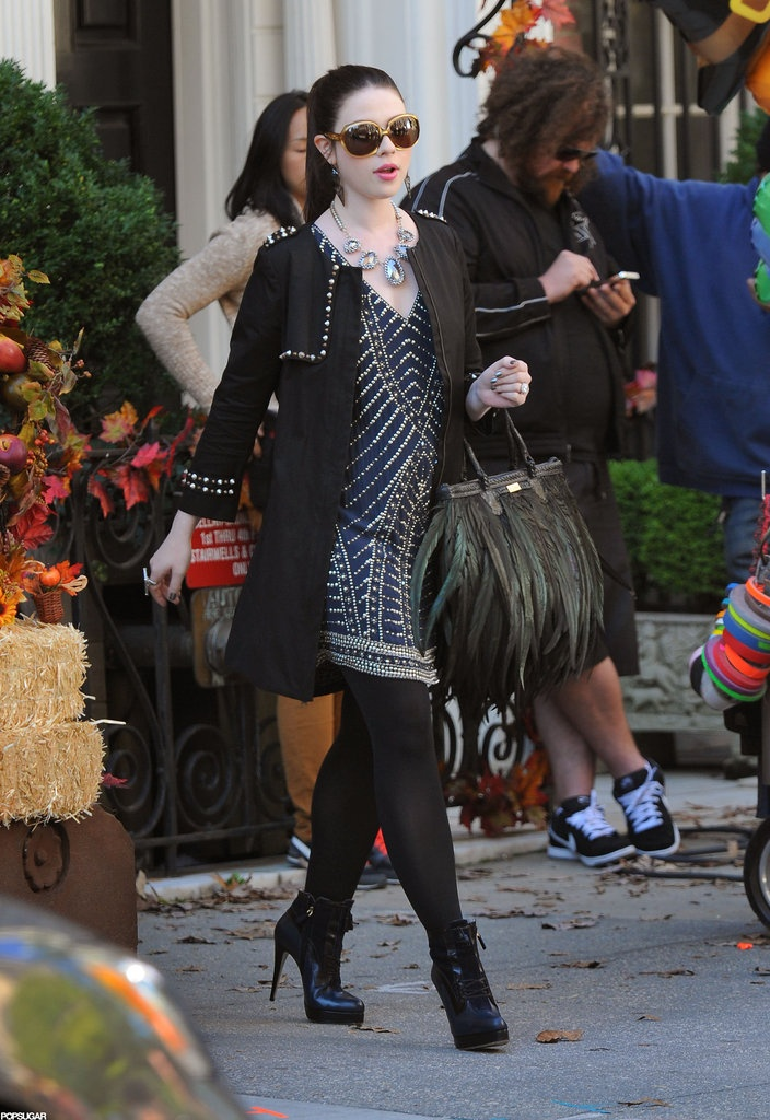 Georgina Sparks: Georgina struts around in a black embellished coat, blue beaded tunic dress, two-tone Jason Wu ankle boots ($1,195), and a lust-worthy feathered Angel Jackson bag.