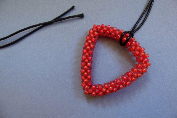 Červený trojúhelník Přívěsek trojúhelník z červeného rokajlu se stříbrným a zlatým průvlekem. Velikost 4,5 × 4,5 cm V ceně černá voskovaná šňůrka 1 m