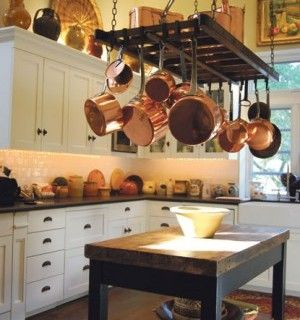 French Copper Pots Hang From An Antique English Bacon Rack In The Kitchen