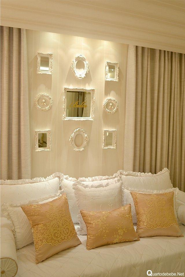 Almofadas dourada com fios de ouro. Na parede vários espelhos com molduras provençais e o nome do bebê gravado no meio do espelho.