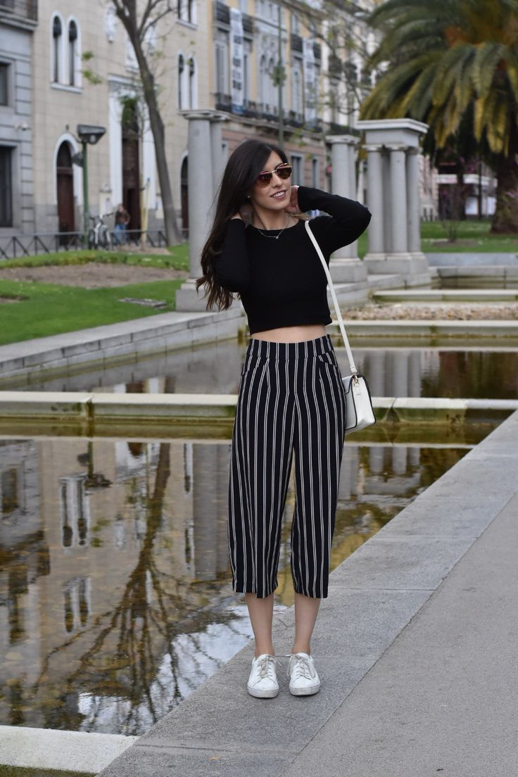 Claudia Peris wearing culottes with stripes, crop top, white bag, and white sneakers, with pink sunglasses and aristocracy necklace (midilema.com)