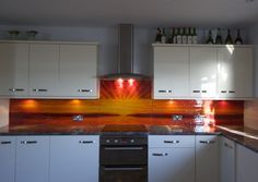 This splashback in Selsey, West Sussex was done for a client who provided a picture to us that they wanted replicated in glass. Naturally, Lisa was all too happy to make it, and the result is as you see. A warm coloured seascape travels across the back of the kitchen, and almost like looking out of the window, one can see all the way to the horizon where the sea meets the sky. These orange colours are made even more vibrant when the sun touches the splashback.