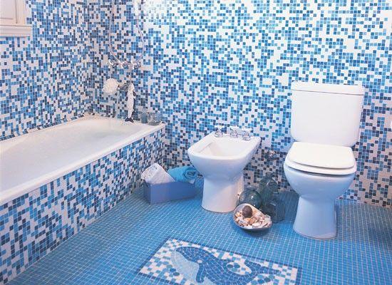Este baño para chicos tiene en el piso un dibujo de una ballena en venecitas azules y blancas, los mismos tonos que se usaron para revestir ...