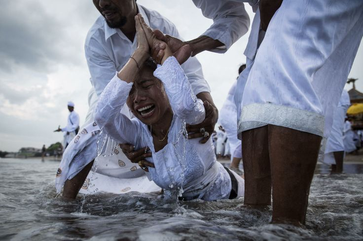 Balinese woman cries while in a state of trance during Melasti Ceremony at a beach on March 28, 2014 in Badung, Bali, Indonesia.