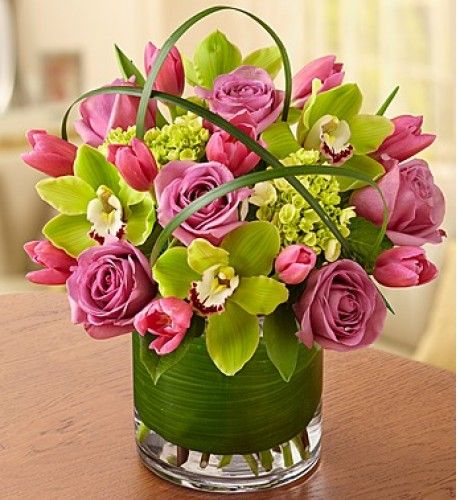 If all the little things they do make you smile, return the favor with this truly original arrangement. Our romantic mix of lavender roses, Cymbidium orchids and tulips is artistically designed with accents of lily grass and tropical leaves and arranged inside a sleek glass cylinder vase to keep you on their mind, always.
