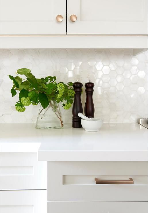 Light gray shaker drawers accented with brass pulls are topped with a white countertop fixed against marble hex floor tiles beneath light gray shaker upper cabinets.