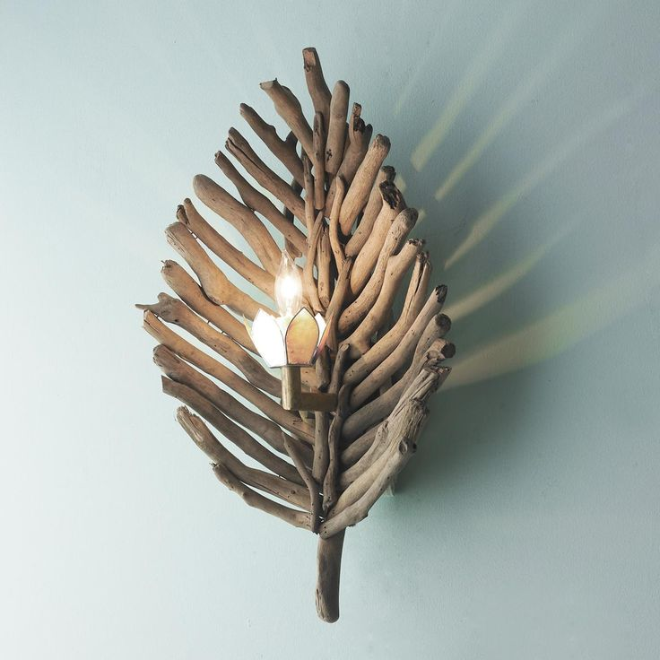 "Driftwood Leaf Wall Sconce A capiz petal bobeche and naturally aging brass hardware add layers of intrigue to this wood leaf wall sconce. Distressed driftwood sticks are reclaimed and used in the natural form in which they are found. One light candle socket. (Approximately 21""Hx12""Wx8""D)"