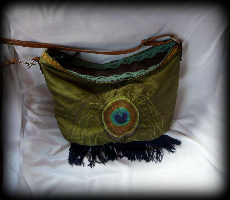 Pávatáska -Handmade by Judy Majoros: Pávatoll ihlette ezt a hímzett női táskát, ami hétköznapi, de akár alkalmi viseletként is hordható. Selyemfényű zöld anyagra hímeztem a pávatollat, belsejébe pedig farmeranyag került, ami tartást ad a táskának. Aljára selyem rojtot varrtam. Két zseb található benne, cipzárral és egy gombbal záródik. Pántja műbőr, mely állítható, így vállon, és keresztben is hordható.Újrahasznosított alapanyagok felhasználásával készült.
