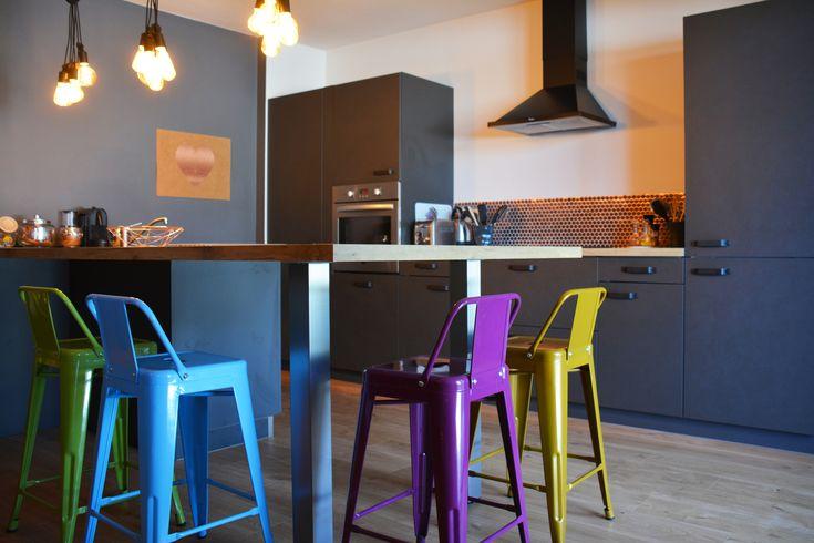 Cuisine tendance couleur noir et bois avec des murs blanc et gris. Les tabourets de bar multicolores apportent de la joie à cet espace de repas en bar
