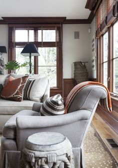 Living room; combination of wood and gray/grey color scheme; chair; sofa; pillows; lamp| Interior design -er: Sam Allen