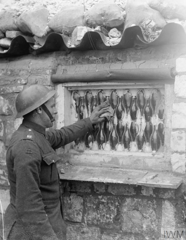 WWI, 22 Feb 1918; The exterior view of a window made from soda water bottles and cement in a dug-out occupied by men of the Royal Engineers near Cambrai. A Sapper cleans the window. © IWM (Q 10698)