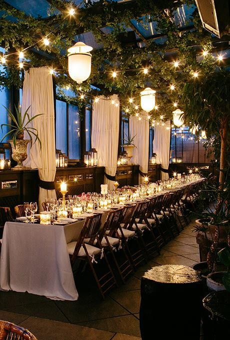 Modern and sophisticated long table setting with lanterns, twinkling lights and overhead greenery ~ http://www.brides.com/wedding-ideas/real-weddings/2014/04/best-wedding-venues-in-the-us