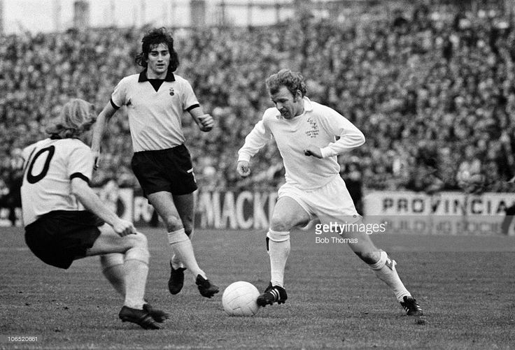 Billy Bremner of Leeds United takes on Willie Carr of Coventry City as Dennis Mortimer looks on...