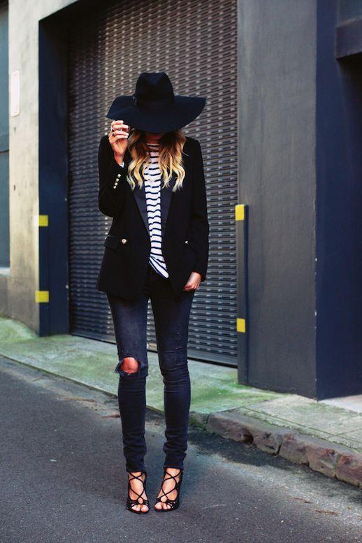 blusa listrada com blazer preto, calça jeans rasgada no joelho e chapéu preto