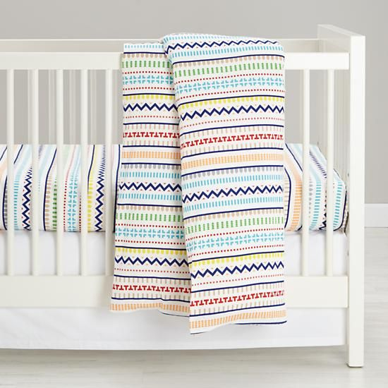 The duvet and crib sheet feature a variety of vibrant shapes inspired by traditional Scottish knitting techniques.