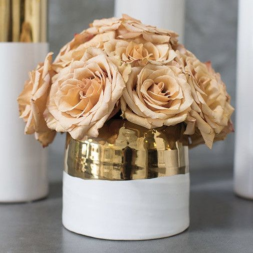 Create an appealing entrance into your home living room with decorative containers, like this ceramic floral pot from the Claire Collection in white with a band of metallic gold at the top. This trend