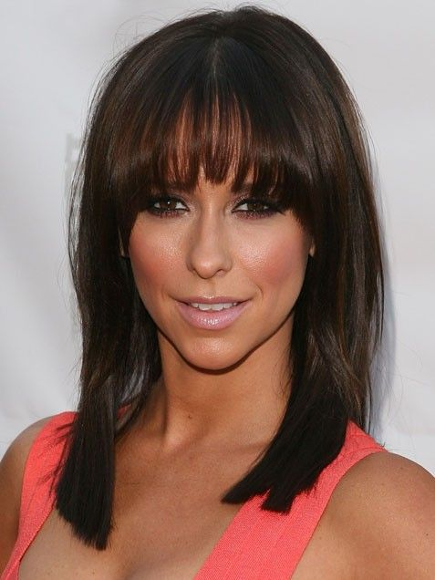 Jennifer Love Hewitt's asymmetrical bangs arc from long on the ends to shorter at the middle...probably looks great pulled up or back too. I wanna get my hair cut like this!