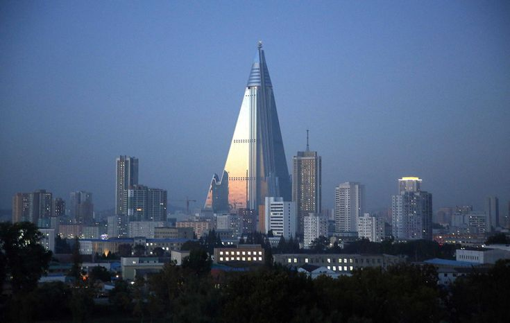 Dusk settles over Pyongyang, North Korea, on October 13, 2015, as the 105-story pyramid-shaped Ryugyong Hotel towers over residential apartments. The hotel has been under construction since 1987 and was intended to be a landmark and a symbol of progress and prosperity, but the economic difficulties that the country went through forced the project into repeated delays. Nearly 30 years later, it has become a major Pyongyang landmark, but has never been used as a hotel as it was intended.