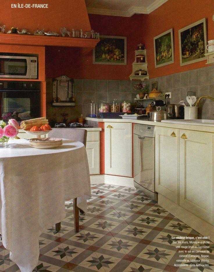 La couleur brique, c'est chic ! Sur les murs, un rouge brun en harmonie avec le sol en carreaux de ciment (Carocim). Nappe, vaisselle et tableaux chinés. Accessoires (Gris Anthracite).