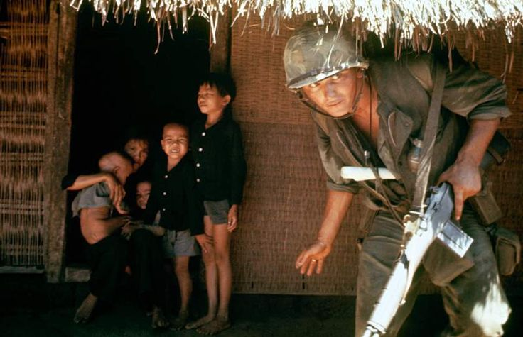 """Within the village children shrink from a scout hunting the V.C. who strike from tunnels under huts."" 1965. Photo by Paul Schutzer. ~ Vietnam War"