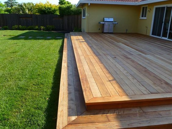 Low deck with two steps. I love how this is simple, level and runs nearly the length of the house. SO much room for entertaining!