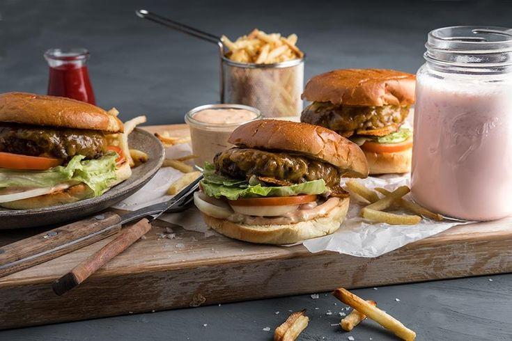 Amerikansk cheeseburger med friter og hjemmelaget jordbær-millkshake   Dette trenger du til 4 personer:  1 pose pommes frites 60 g majones, gjerne amerikansk type av merket Hellmann´s 2 ss ketchup + mer til dipping 1 ss agurkmix 1 gul eller rød løk 1 isbergsalat 1 stor bifftomat 1 ss nøytral olje, til steking 4 hamburgerbrød 4 ss sennep 4 Grill perfekt-hamburgere 4 tykke skiver cheddarost    Milkshake:  200 g jordbær, gjerne ferske 400 g vaniljeis 4 dl melk