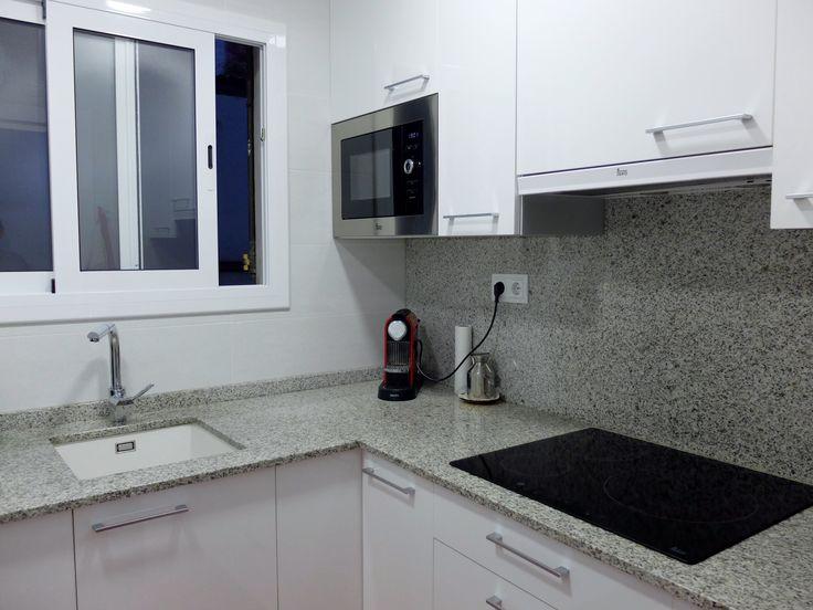 reforma de cocina con encimera de granito y muebles blancos brillante con tiradores por accesible