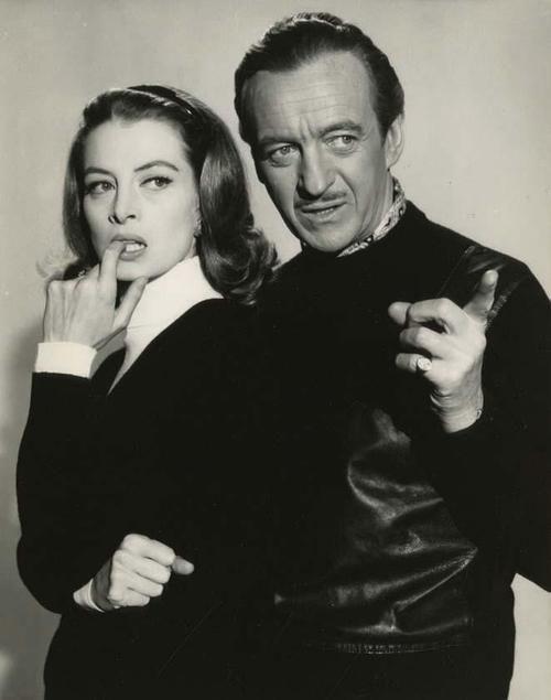 """Capucine no parece muy convencida de lo que le señala David Niven en esta foto publicitaria para """"La Pantera Rosa"""", 1963"""