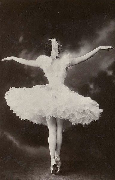 Anna Pavlova in her signature role, The Dying Swan. Her feet were so severely arched, she had to invent her own reinforced shoe. It is rumored that she would retouch her photographs to make her pointe shoes look like those favorable of the era.