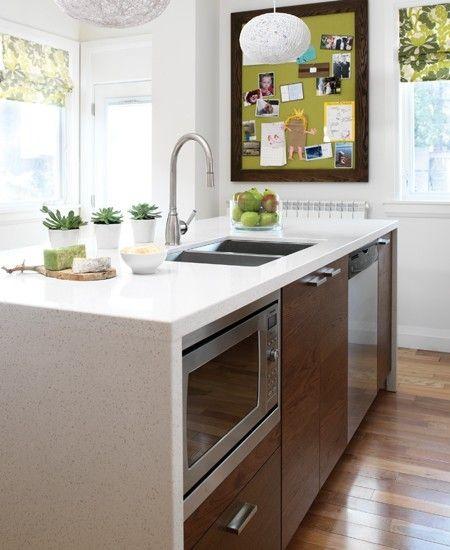 Peignez votre babillard pour une touche de couleur.  Cette cuisine compacte était serrée et dysfonctionnelle, avec des étagères pêle-mêle et du rangement mal disposé. Une couche de peinture blanche rafraîchit la pièce et l'ilot placé au centre de la cuisine facilite la circulation et intègre habilement un micro-ondes et un lave-vaisselle.