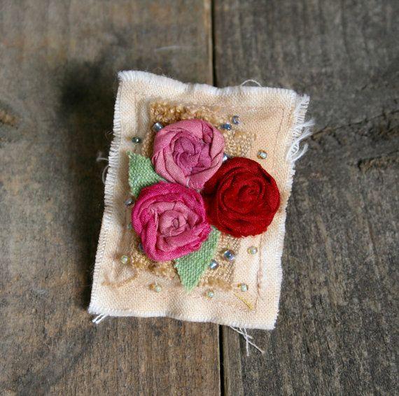 Un broche hecho a mano bonito y romántico estilo vintage, té teñido calico con rosas de seda de sari y una dispersión de granos de la semilla.  Mide aproximadamente de 5,5 cm por 4,5 cm.