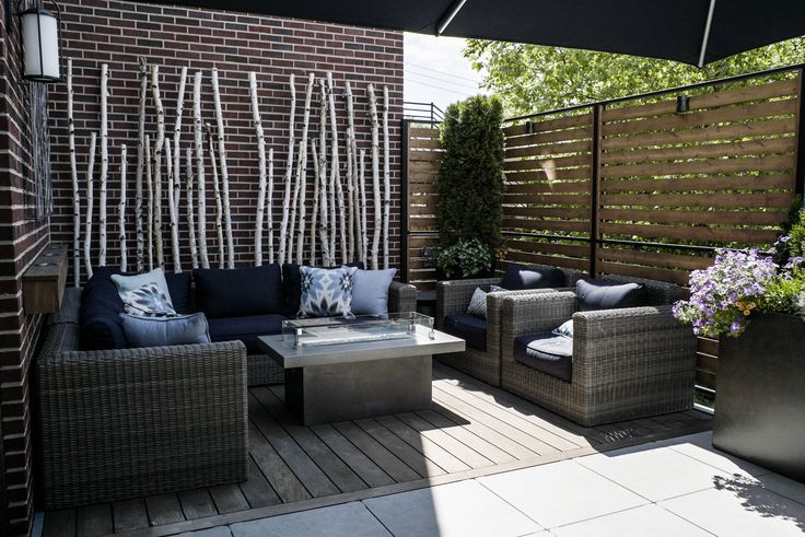 Small back porch Roof Deck in Lincoln Park, Chicago.  Birch poles, evergreens, and seasonal flowers help to create a layered effect which softens the appearance of the walls