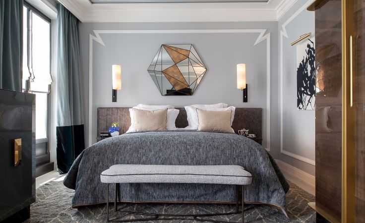 Bedroom in gray with an exquisite mirror design over an elegant bed.