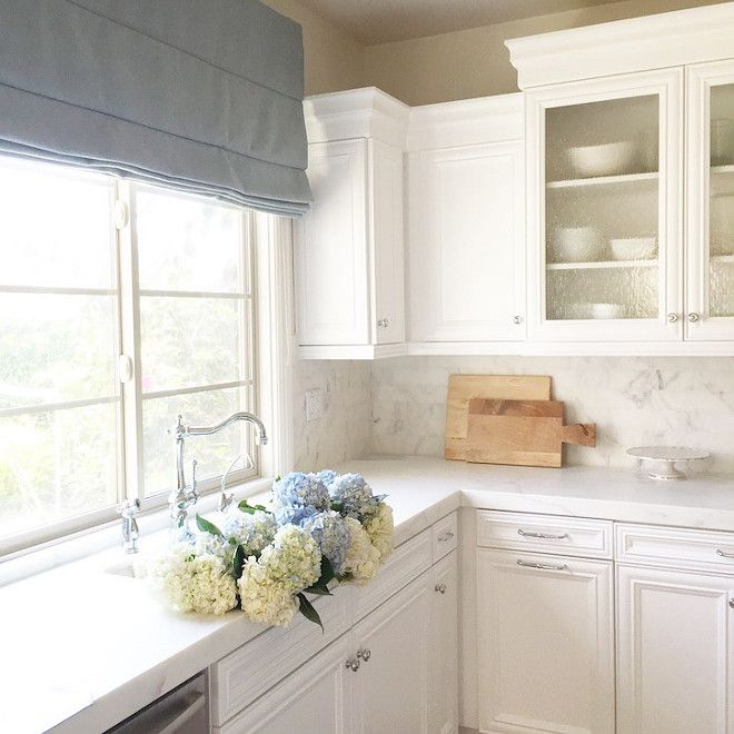 Kitchen sink. White kitchen sink ideas. A blue Roman shade brings softness and a touch of color to this white kitchen.  The fabric is a Schumacher blue linen and the faucet is by Rohl.   Kitchen sink. Kitchen sink #Kitchensink #Kitchen #Sink Becki Owens