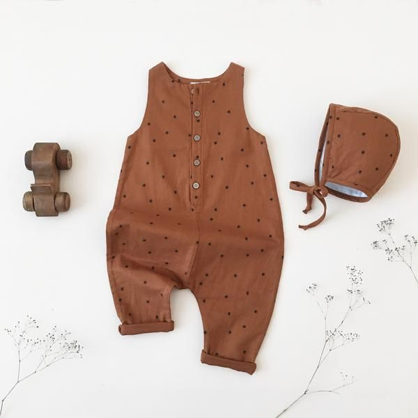 Rust jumpsuit with all-over star print.  5 wooden buttons at front.  Back pockets.  Relaxed fit. Made of 100% cotton handloom woven.    CAREINSTRUCTIONS Machine