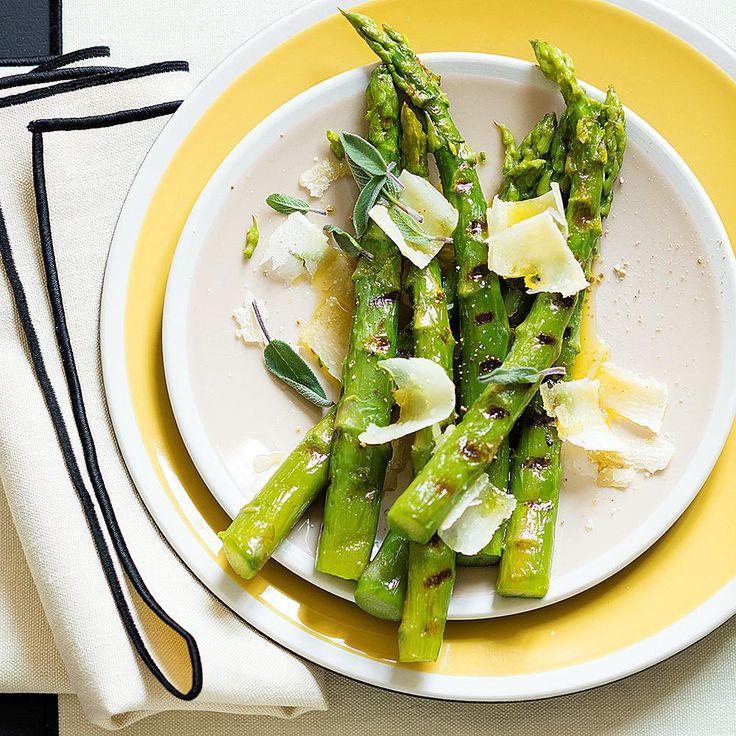Faire chauffer un grand volume d'eau salée. Éplucher rapidement les asperges, puis les faire cuire dans l'eau pendant 10 minutes. Les égoutter, puis les faire griller à la poêle avec 1 cuillerée d'huile d'olive. À l'aide d'un économe, détailler des copeaux de parmesan. Au moment de servir, déposer les asperges dans un plat, les parsemer généreusement de copeaux de parmesan, les arroser avec l'huile d'olive restante, et poivrer selon votre goût.