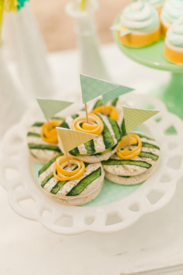 such cute tea sandwiches with cheese spread and cucumber slices in dramatic pattern with a lemon peel garnish