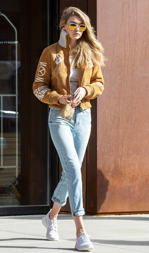 Gigi Hadid wears light wash denim, white sneakers, and a camel suede bomber jacket.