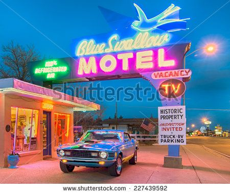 TUCUMCARI, NM/USA - MAY 9, 2013: Twilight at the historic Blue Swallow motel on Route 66. A 1970 Ford Mustang classic car is parked under the iconic neon sign.