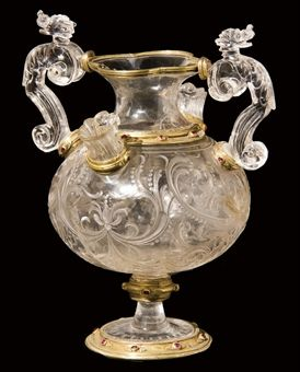 A SILVER-GILT- AND RUBY-MOUNTED ROCK CRYSTAL VASE MILANESE, LATE 16TH OR EARLY 17TH CENTURY The quadrilobe mouth supporting two scrolling handles each surmounted by a dragon head, the bulbous body with two fluted spouts and carved overall with scrolls, on a circular stem and spreading circular foot, the silver-gilt mount to the foot engraved to the underside '188' and 'VI', 'VII', 'VIII'; $681,947.00
