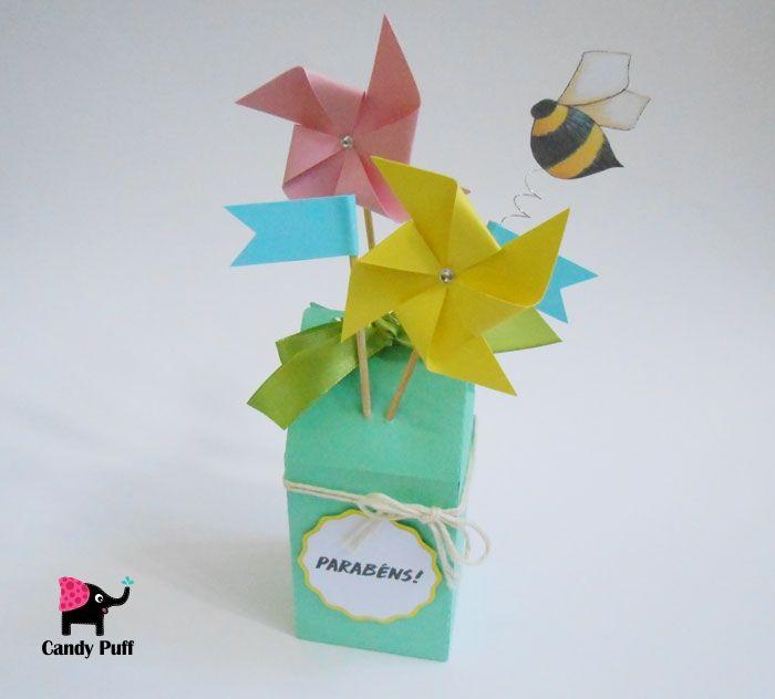 """Embalagem criativa que contém no seu exterior um label com a palavra """"Parabéns"""". Nesta embalagem são visíveis duas ventoinhas, assim como duas bandeiras e uma abelha. O interior contém 100 gr de bombons de chocolate de leite."""