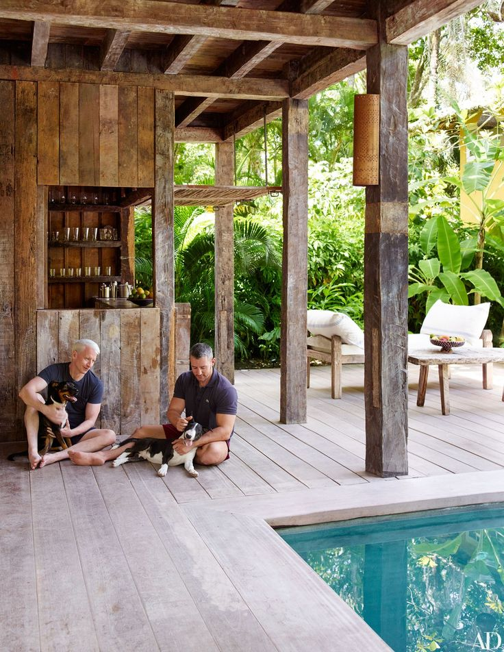 Cooper and his partner, Benjamin Maisani, relax with a neighbor's dogs, Caia (left) and Tim, on the pool terrace, which Wilbert Das lined in tatajuba planks and equipped with an Uxua Casa pierced-metal sconce.