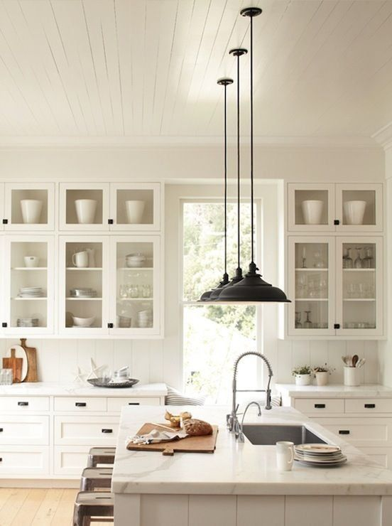 White kitchen cabinets with glass doors, wood floors, white marble counter tops